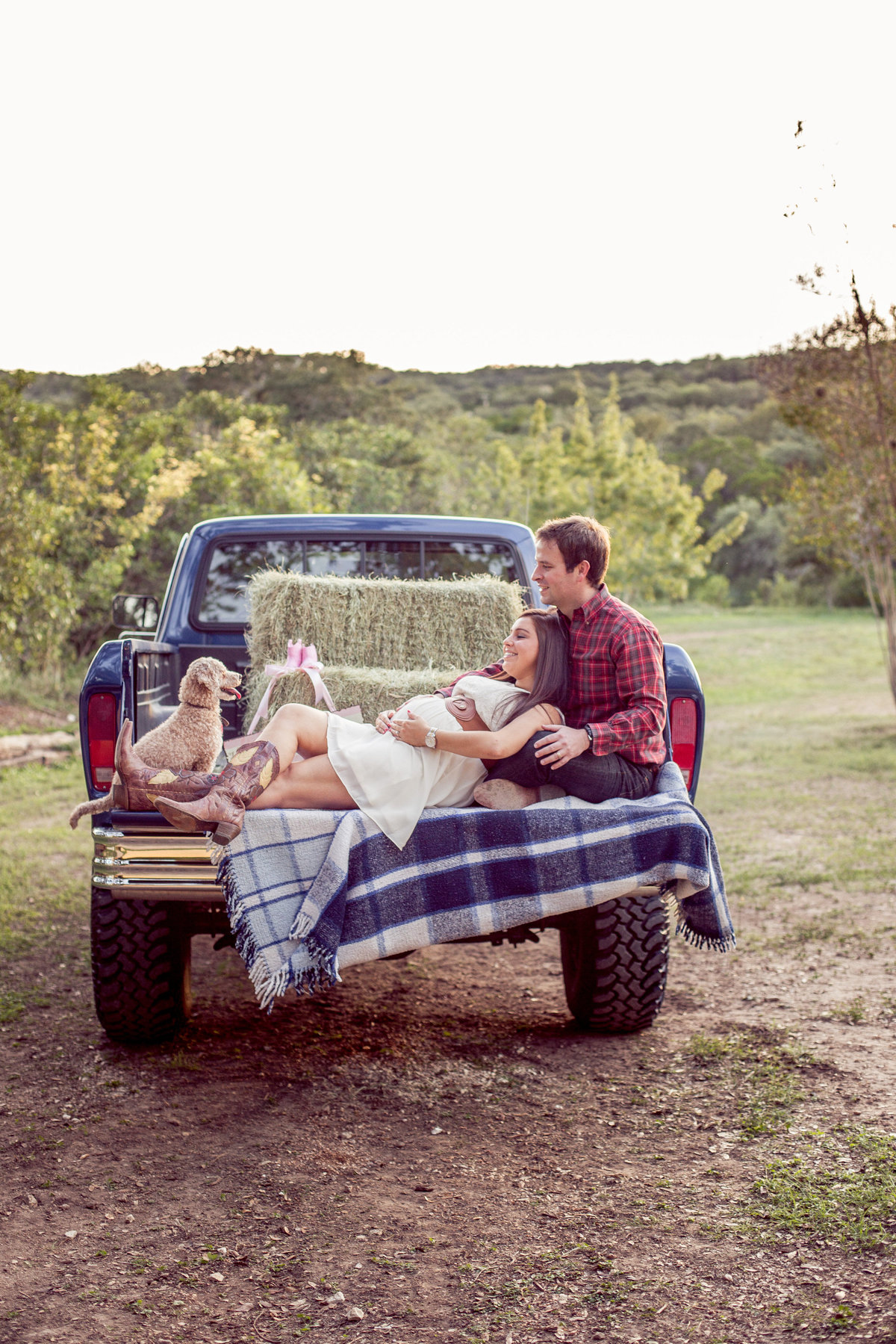 Expecting couple laying in the back of a truck with hay bales for their maternity photography session in San Antonio
