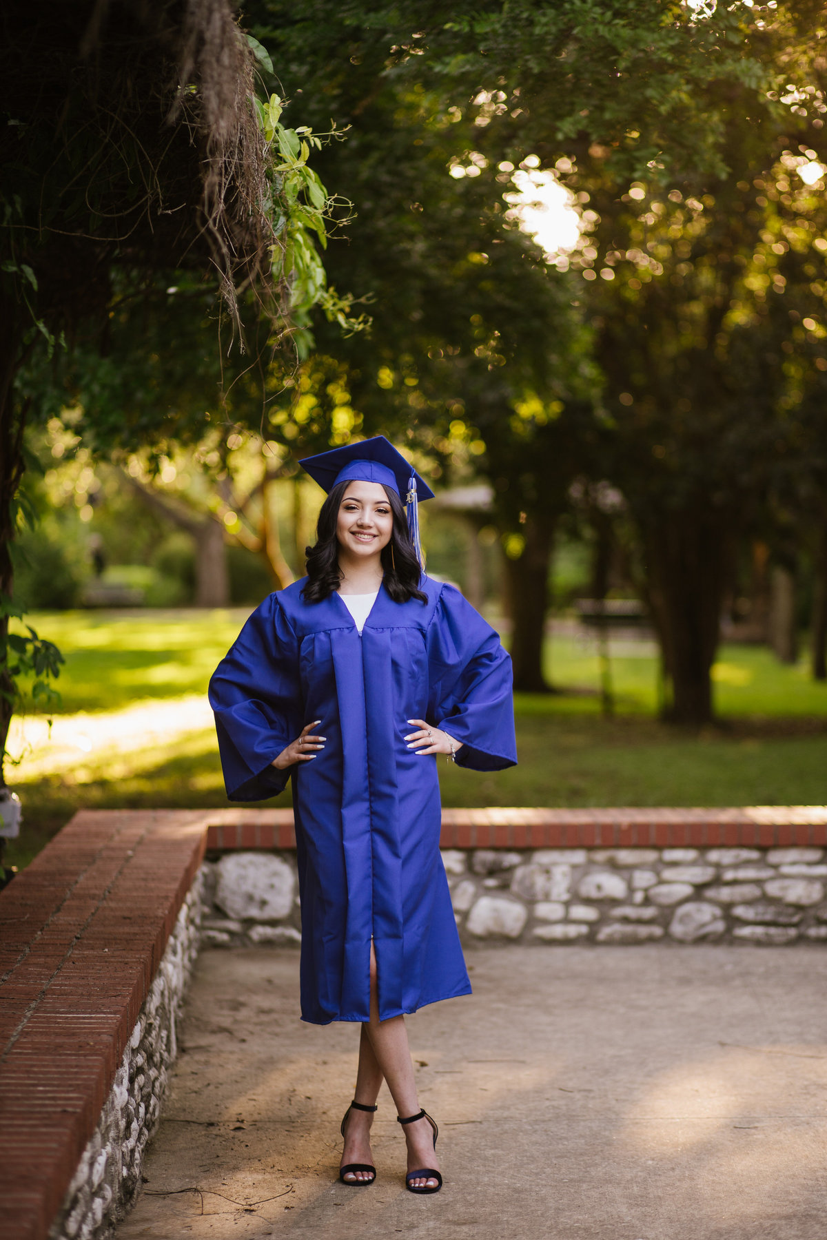 San Antonio high school senior girl in cap and gown with hands on hips by senior photographer