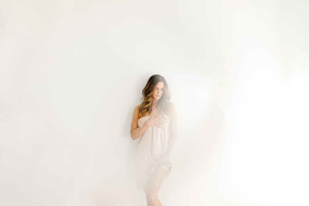 Lady in a white studio during bridal boudoir session