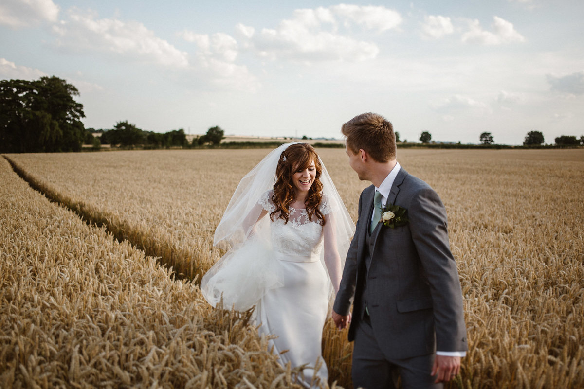 Bride & Groom walking through corn field by Jono Symonds Photography