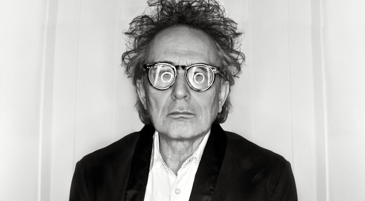 Portrait Musician Marc Jordan swirl of circle lights in reflection of his glasses against white backdrop black and white image