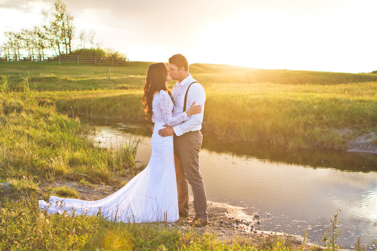 couple standing in a field with a creek behind