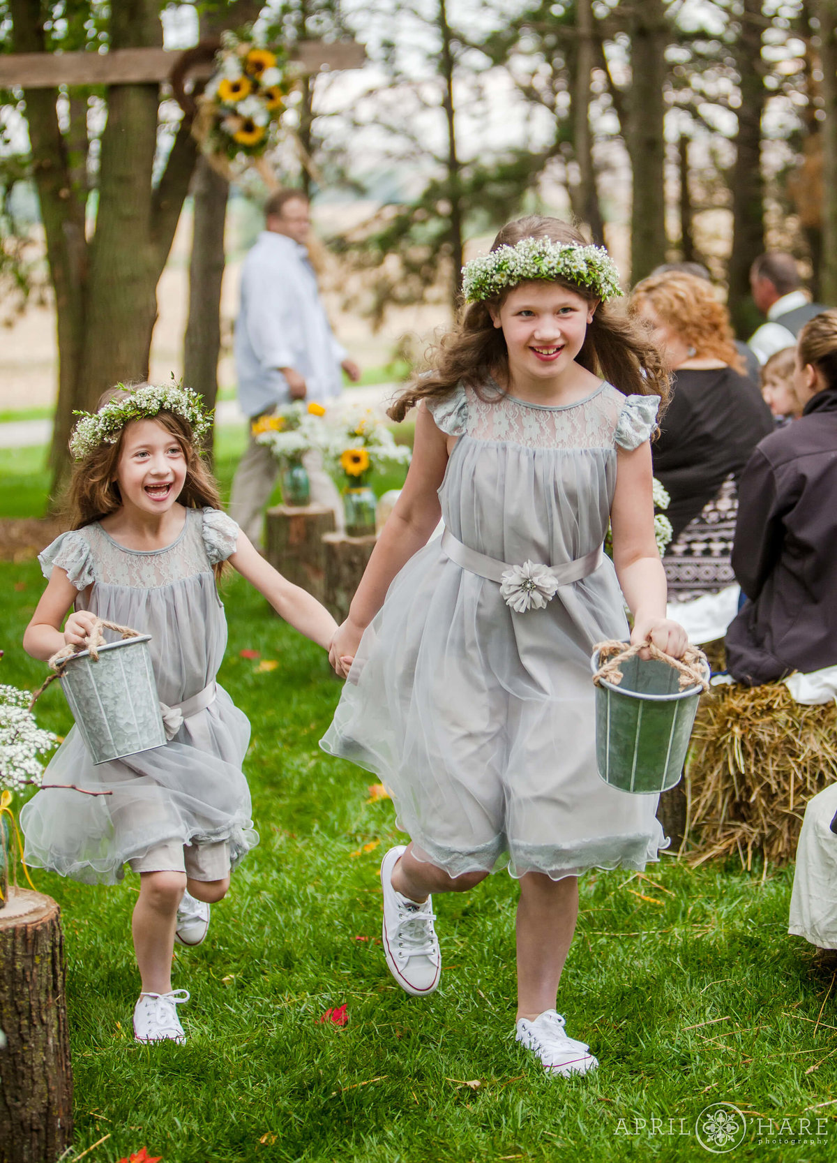 Cute flower girls wearing flower crowns run down the aisle at a private Nebraska Farm Wedding