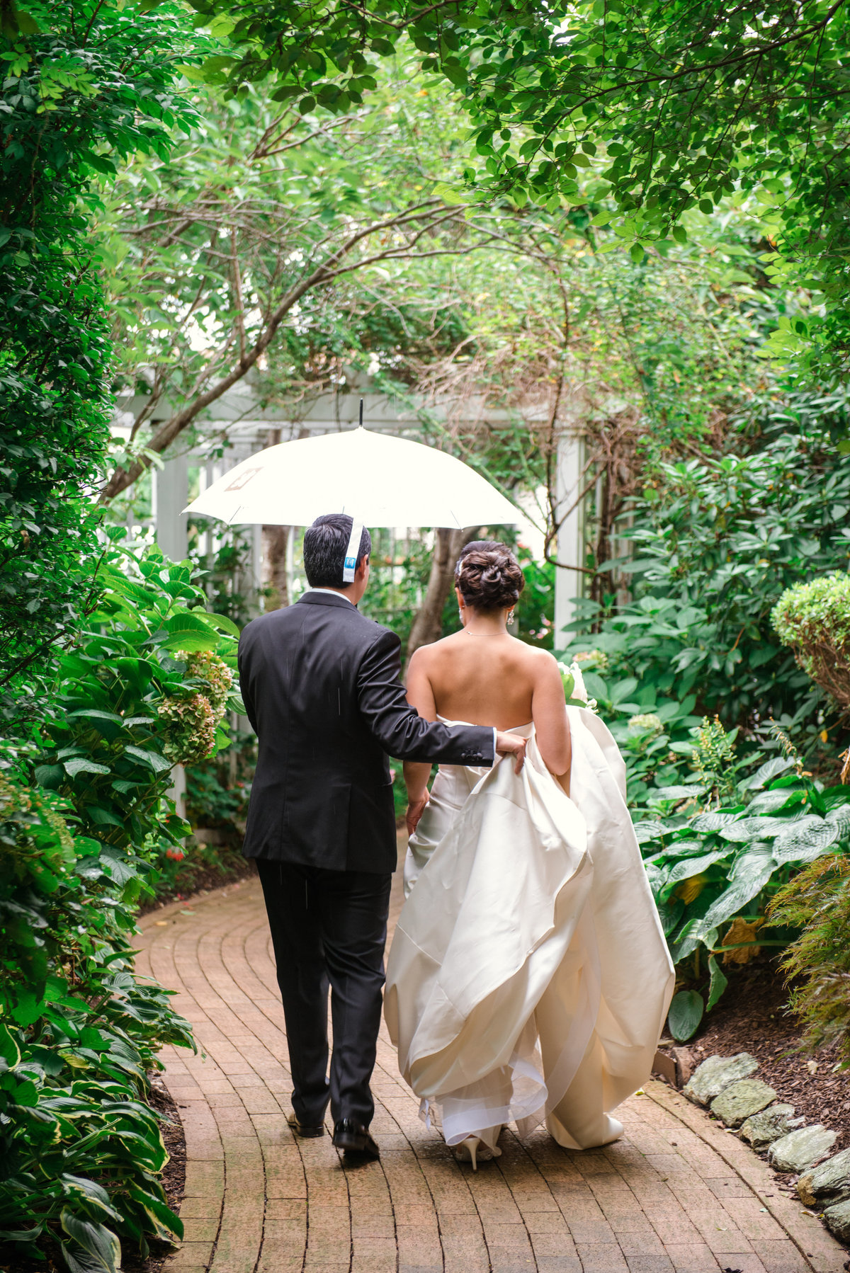 photo of groom holding umbrella and walking with his bride outside The Garden City Hotel