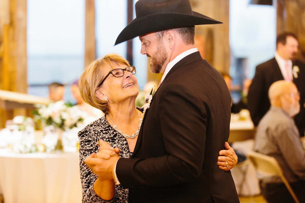 A mother dances with her son at a wedding reception inside a barn.