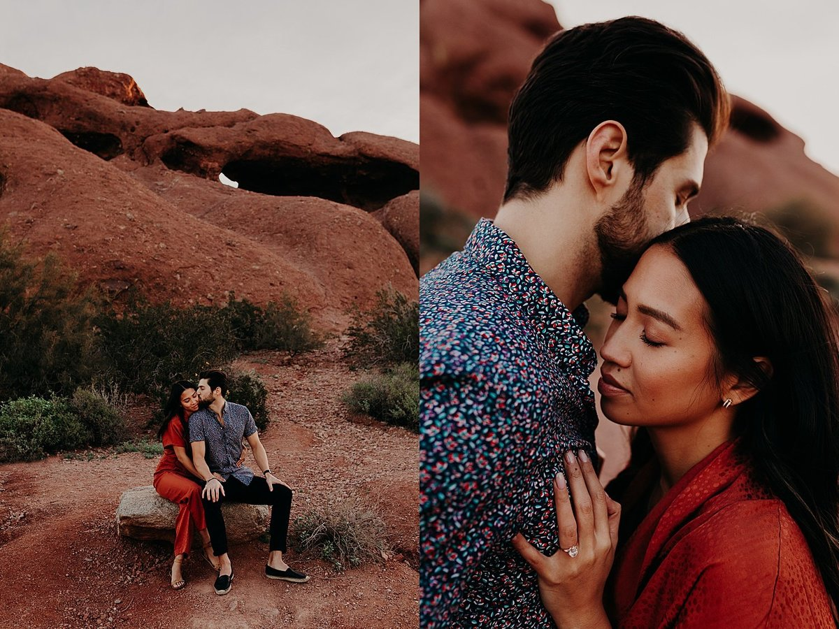 Husband and Wife sit on large rock together while cuddling