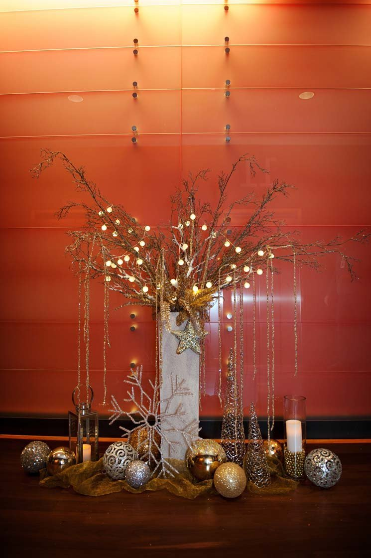 large holiday decoration piece in large white stone planter with tall light branches, gold sparkle hanging strands, large gold ornaments and lanterns at base