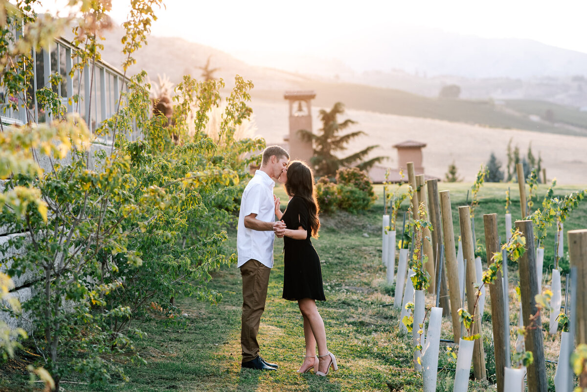 Couple holding hands and kissing at Larc Hill Vineyard in Chelan, WA
