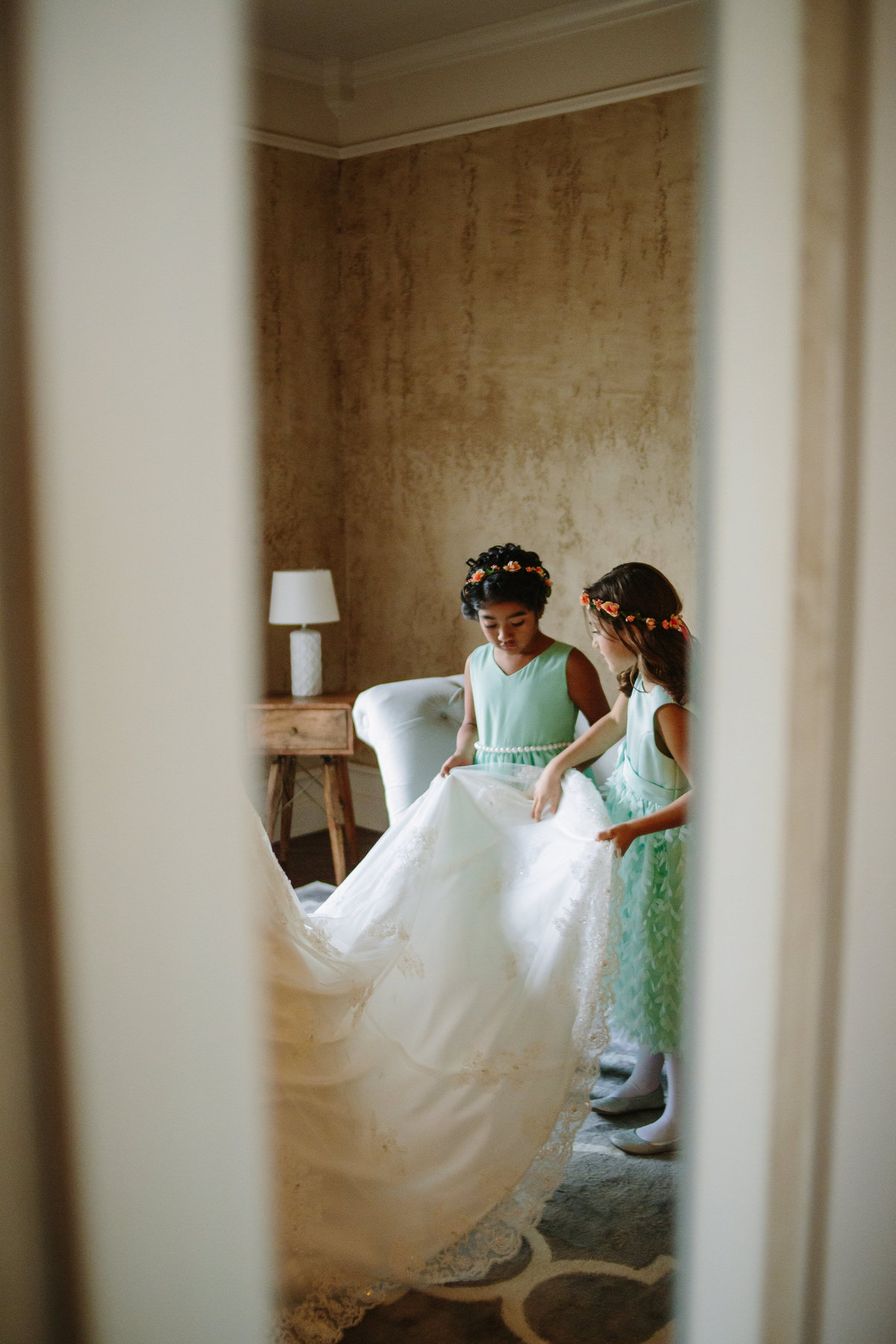 Flower girls checking out bridal gown before wedding while getting ready