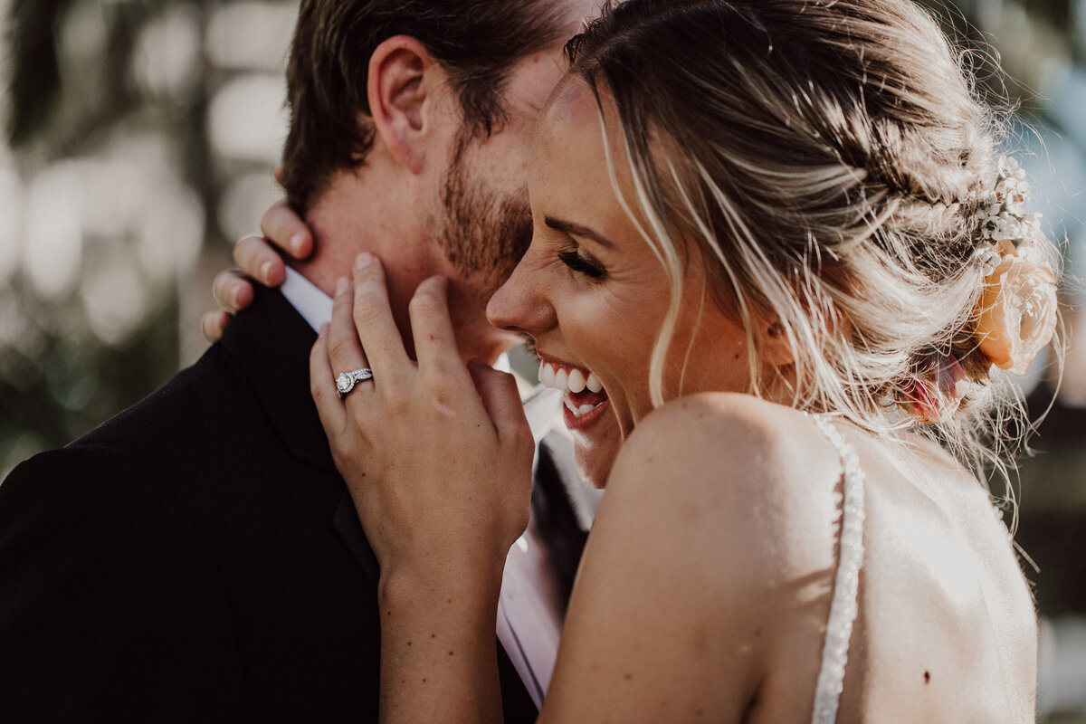 Groom-whispering-in-brides-ear-making-her-laugh