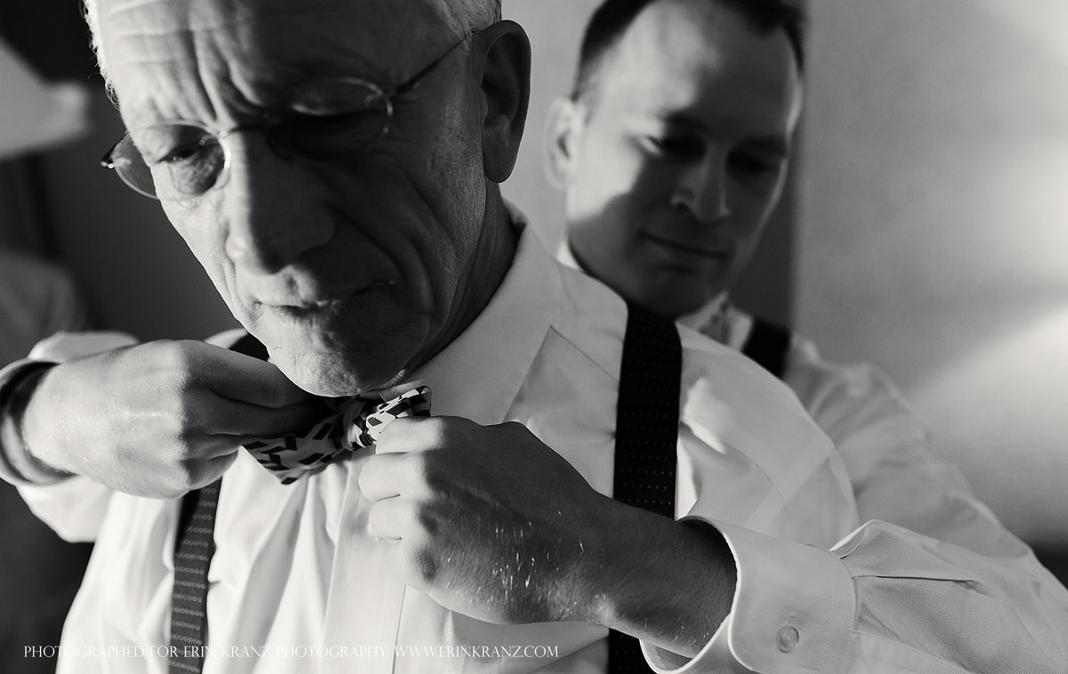 charlotte wedding photographer jamie lucido captures documentary of the men getting ready- the groom adjusts his father's tie from behind