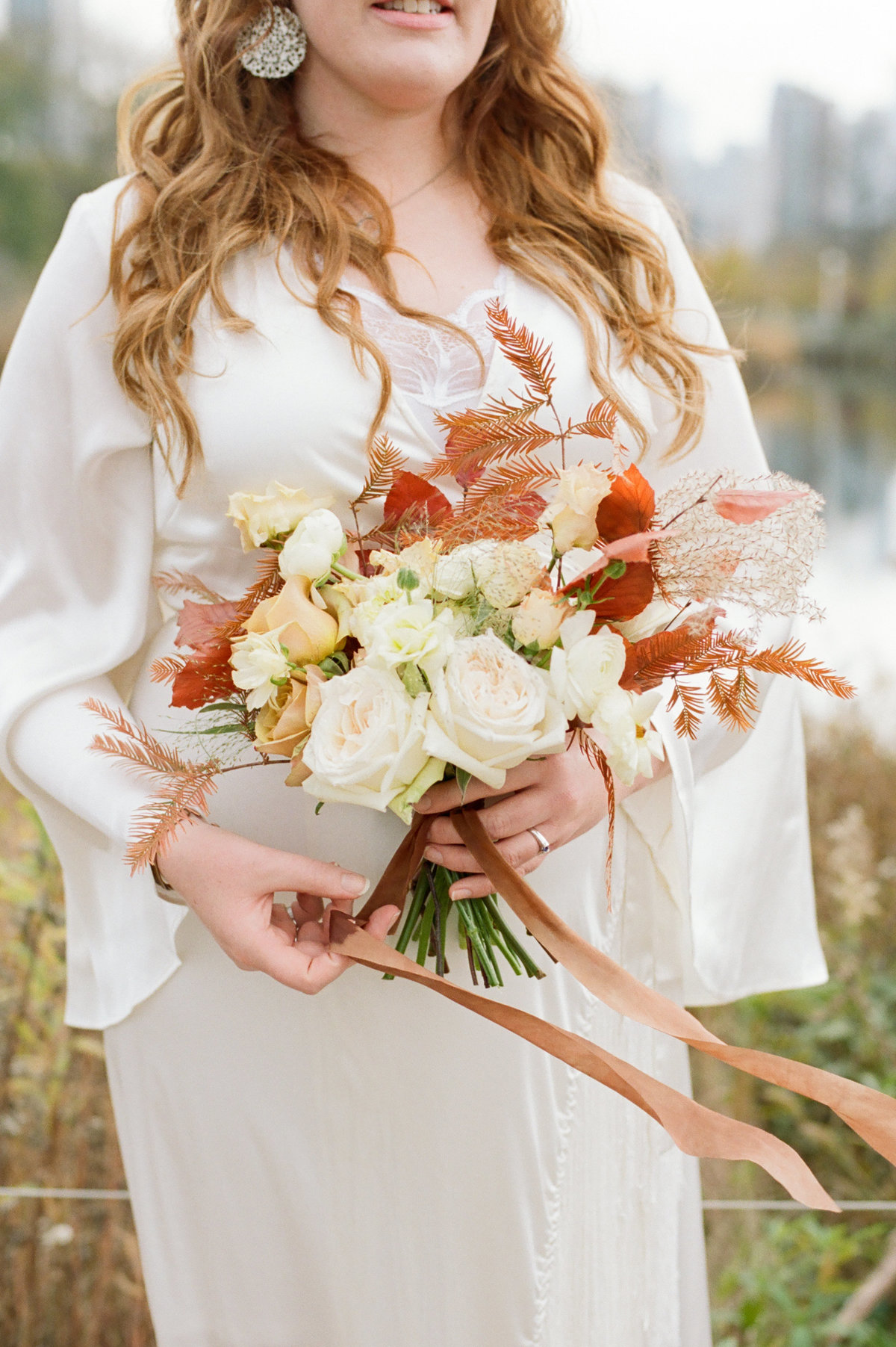 bride holding rustic fall bouquet with flowing ribbon