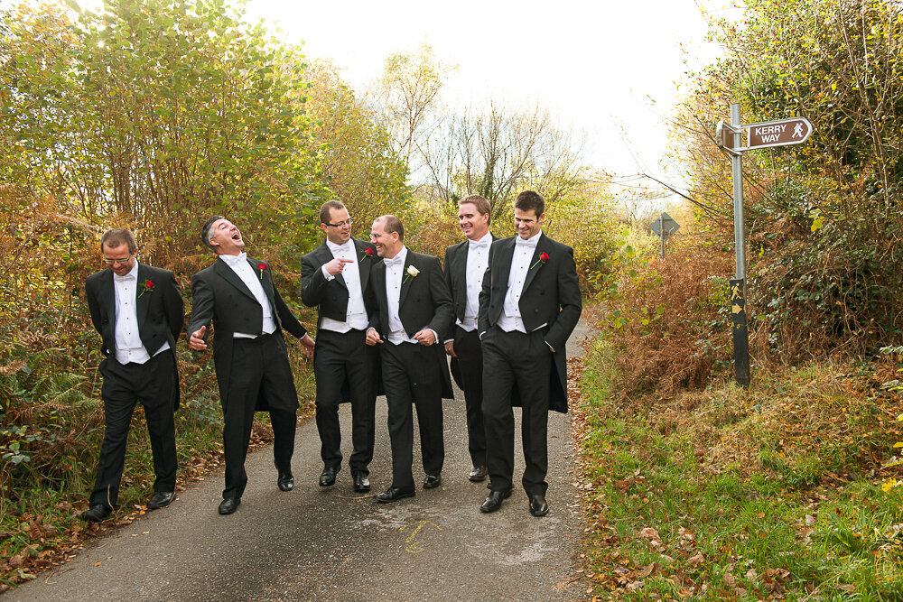 Groom and groomsmen in white tie and black tailcoats walking together on country road laughing