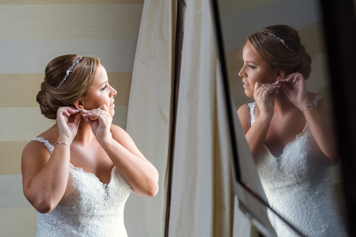 Bride putting in earrings looking out the window at The Inn at Fox Hollow