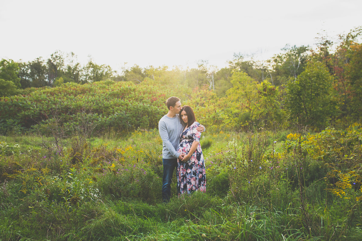 pregnant couple hugging in field {Burlington Maternity Photographer}