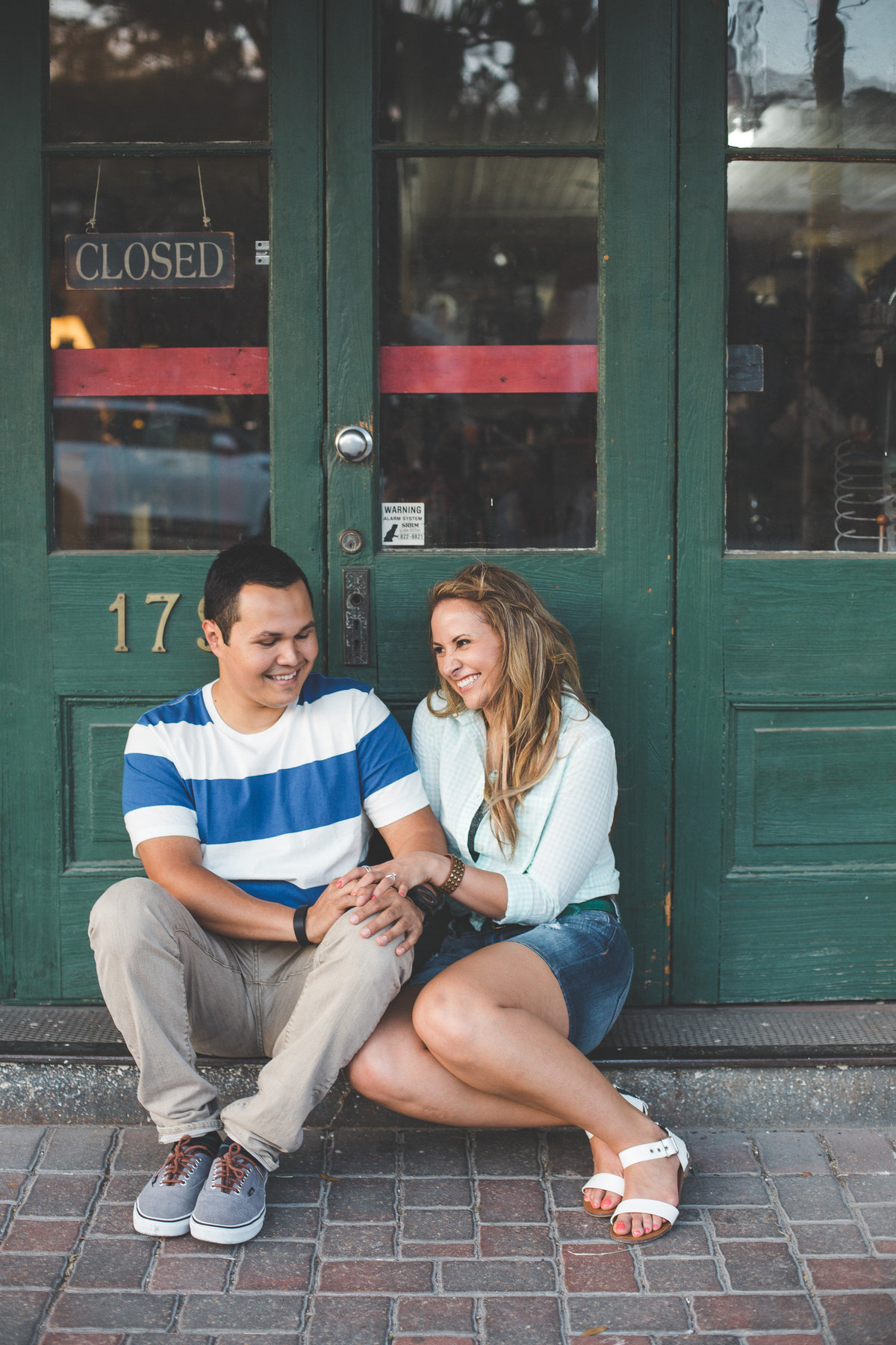 Engaged couple sitting in on cobblestone path in front from green door holding hands.