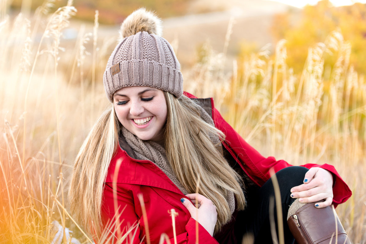 senior girl looks off camera candidly during fall senior session at snowbasin