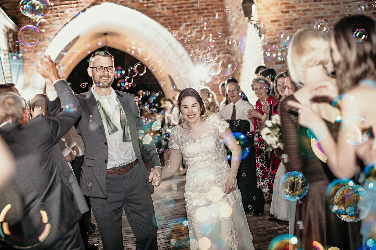 A photograph of the bride and groom holding hands, smiling and celebrating as they exit their wedding reception while the guests surround them and bubbles fill the air by Garry & Stacy Photography Co - Sarasota Florida wedding photography