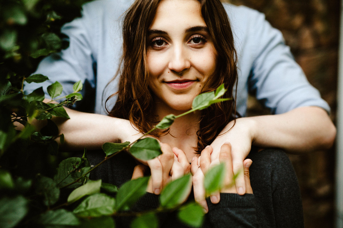 portrait of woman behind leaves holding boyfriends hands