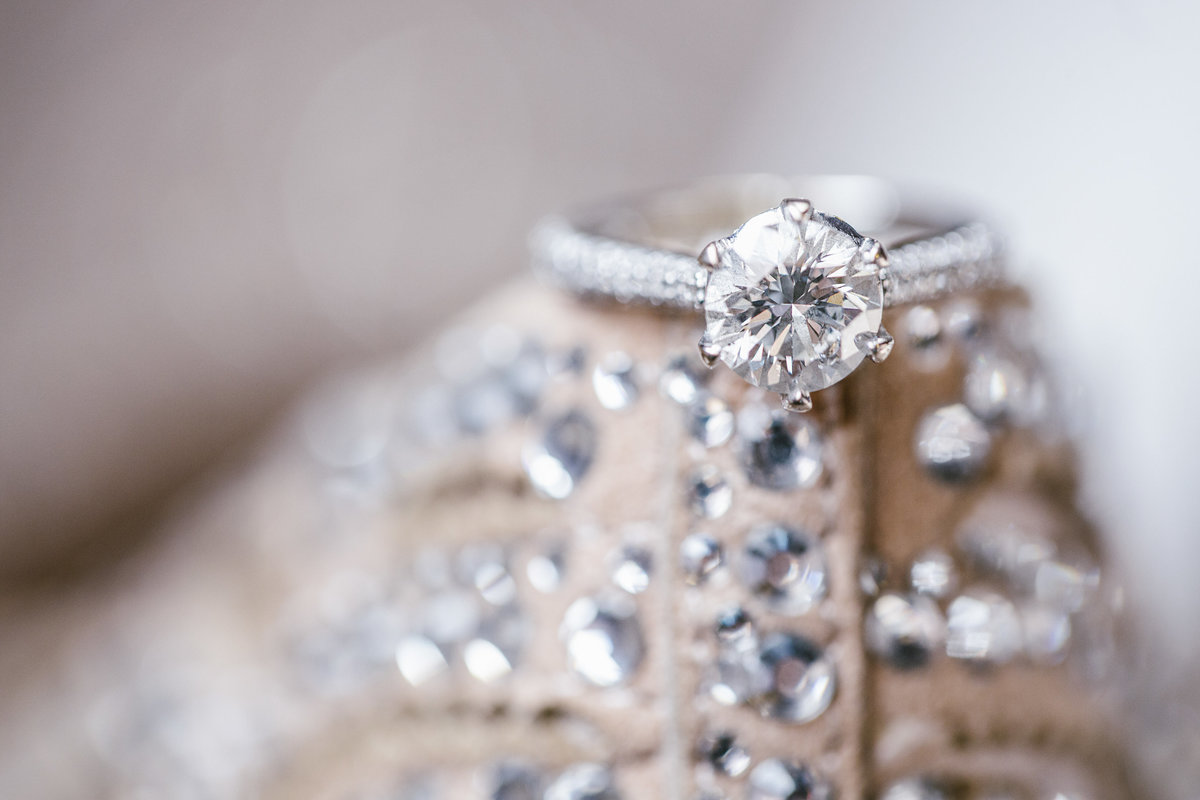 engagement ring sitting on brides wedding shoes