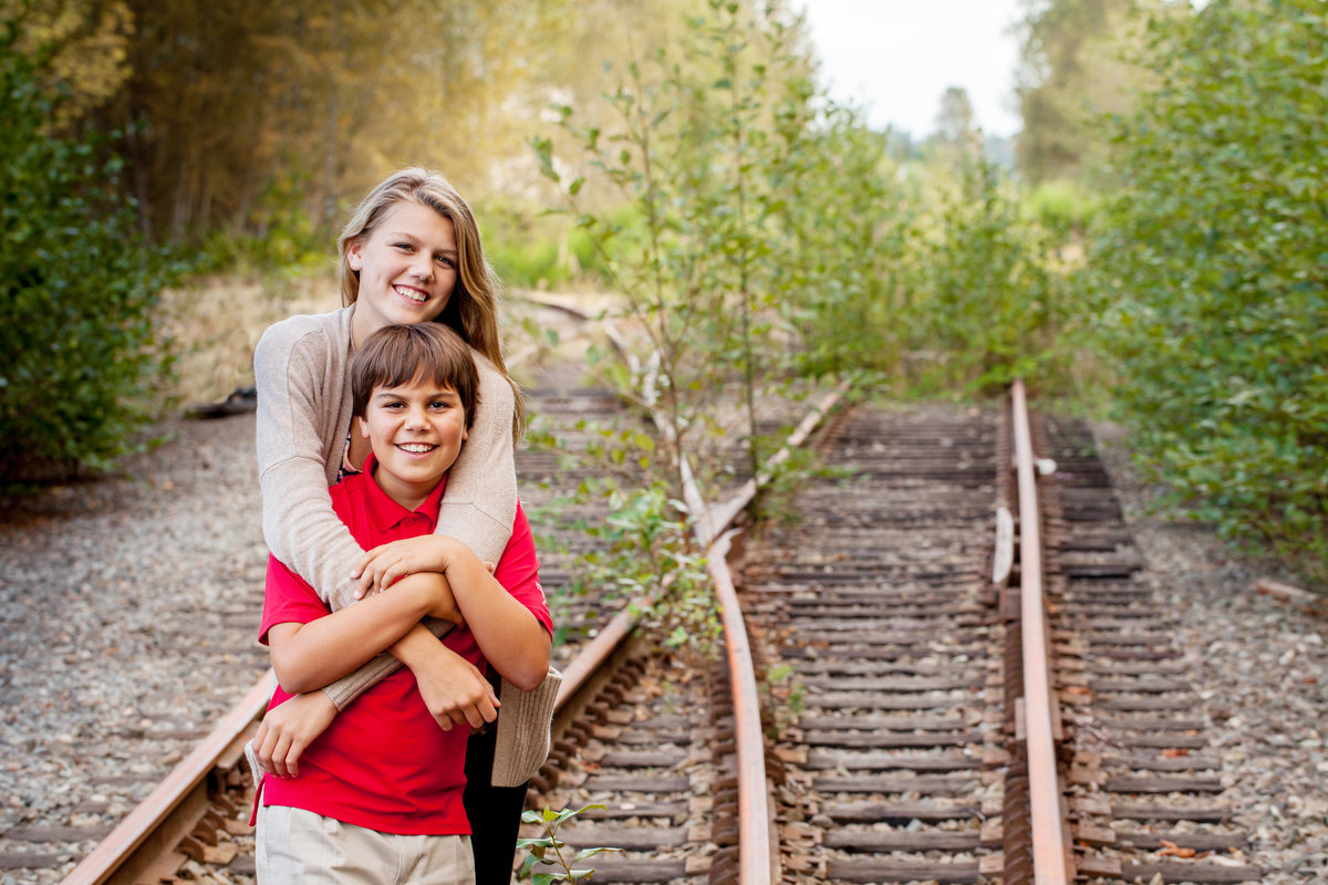 Sibling posing for portraits on dead tracks in Bellevue, WA