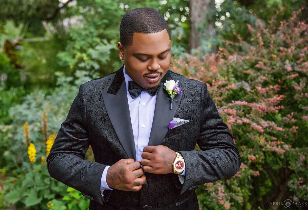 African American Groom with tattoos in a black tux preps for his wedding day at Denver Botanic Gardens in Colorado