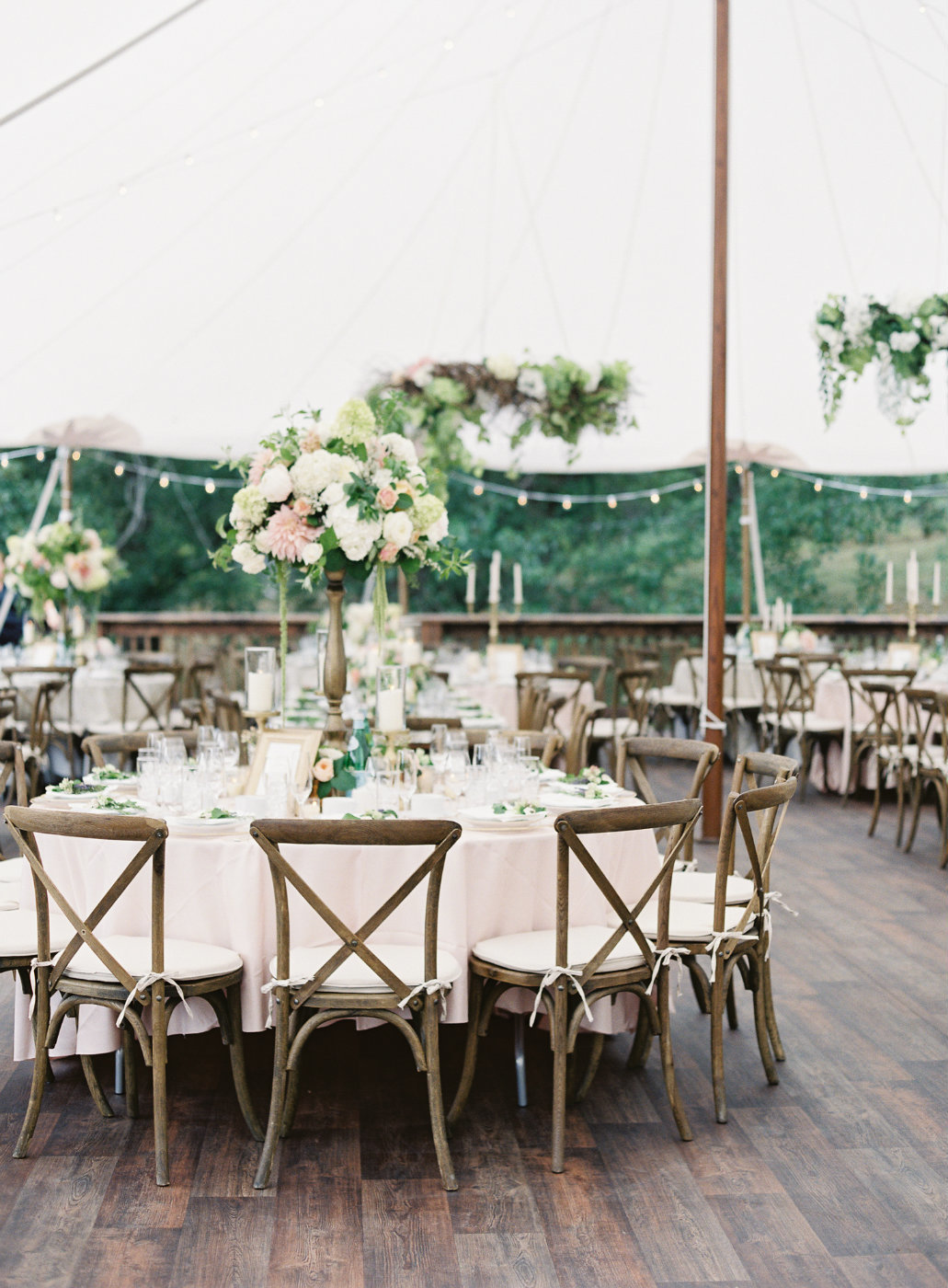 Luxury custom white  tent with wood floors and garden style floral designed by Flora Nova Seattle.