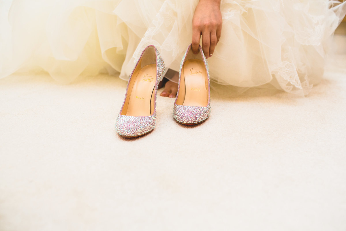 bride putting on her christian louboutin aurora boreale wedding shoes