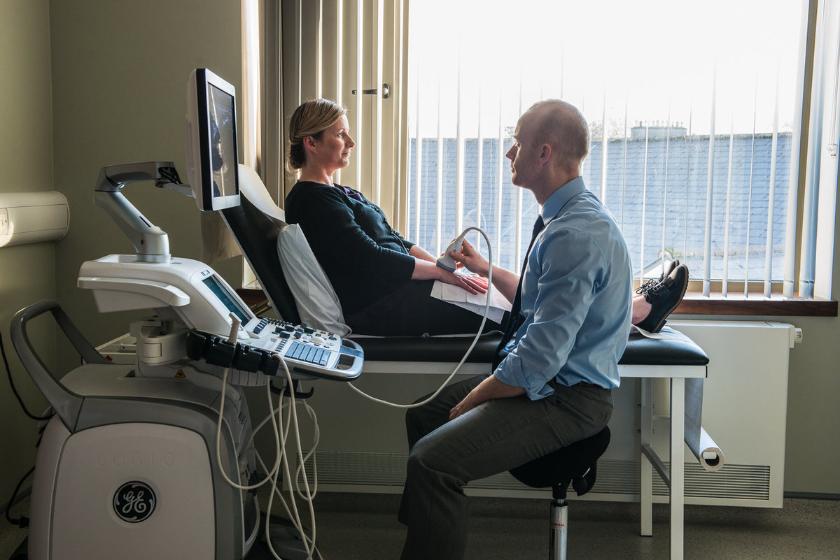Doctor ultrasound scanning patient