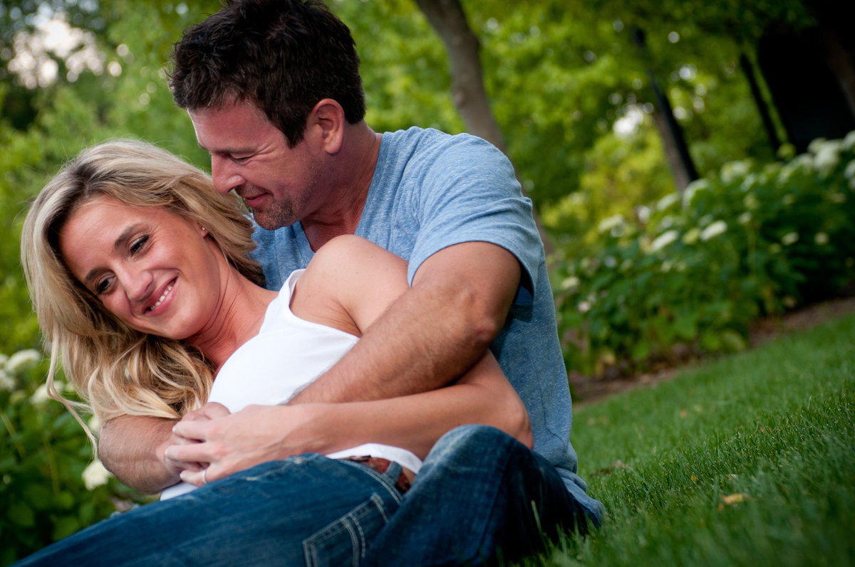 snuggling engagement couple on a grass lawn
