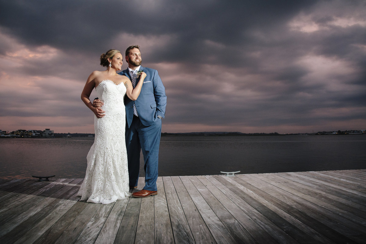 bride and groom at sunset on dock at channel club wedding