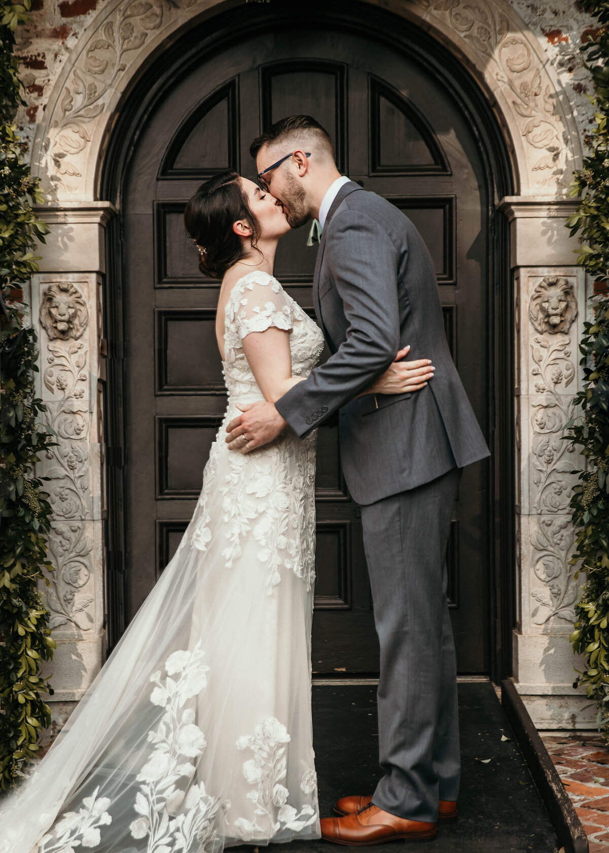 A photograph of the bride and groom romantically kissing as they embrace, standing before a vintage wooden arched door, showing the bride's beautiful dress and train