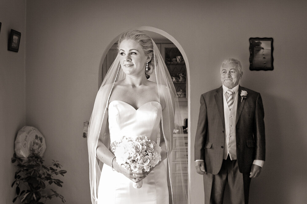blonde bride wearing a mermaid style wedding dress and long veil looking out window while the father of the bride looks at her