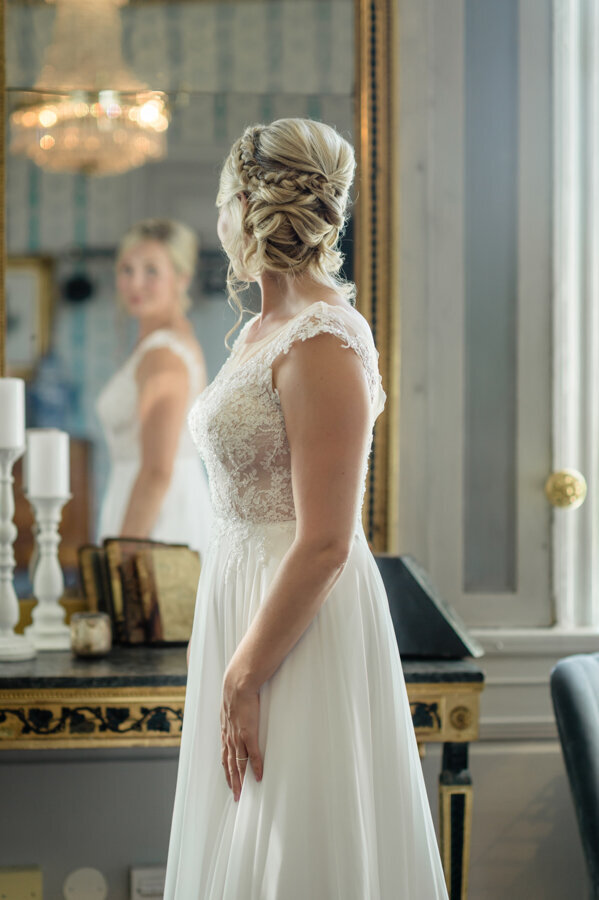 Bride in lace dress, low updo and braid stands in front of a gold and black table and looks at her reflection in a large gold mirror