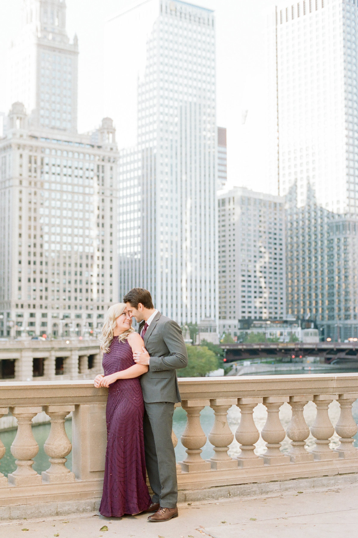 engaged couple in elegant suit and gown in front of chicago skyline