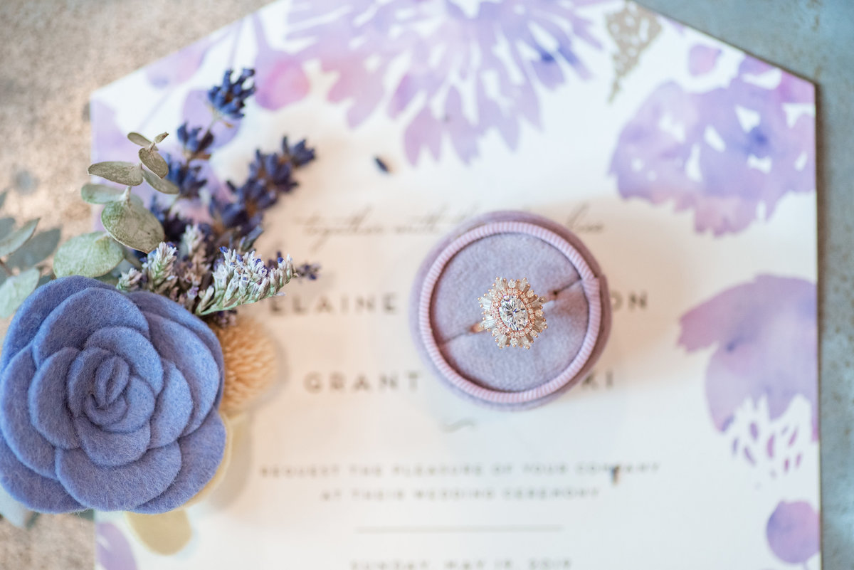 An engagement ring in a lavender velvet ring box on a lavender wedding invitation.