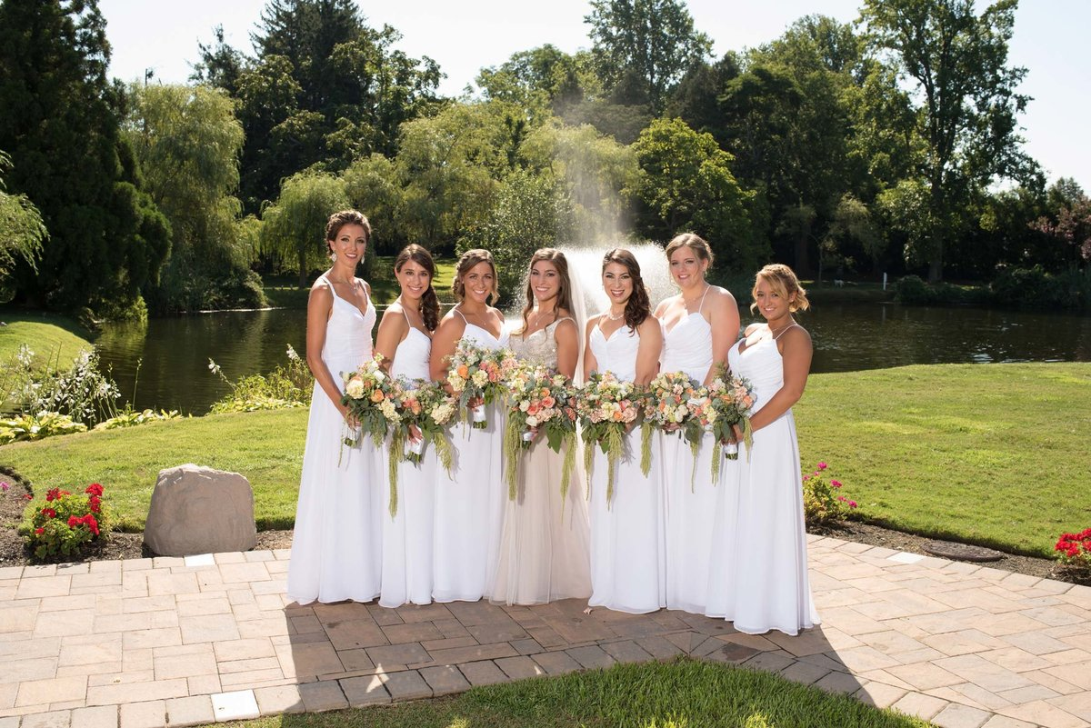 Bride and bridesmaids holding bouquets outside at Flowerfield