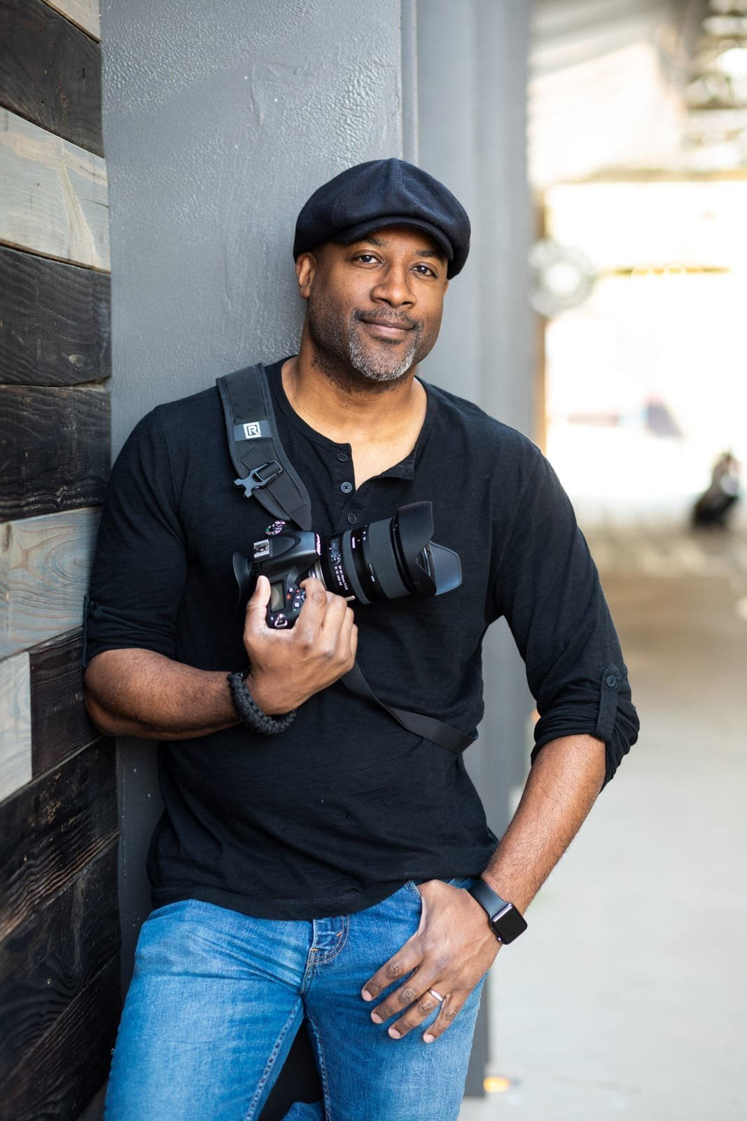photographer holding nikon camera on black rapid strap leaning on wall Atlanta