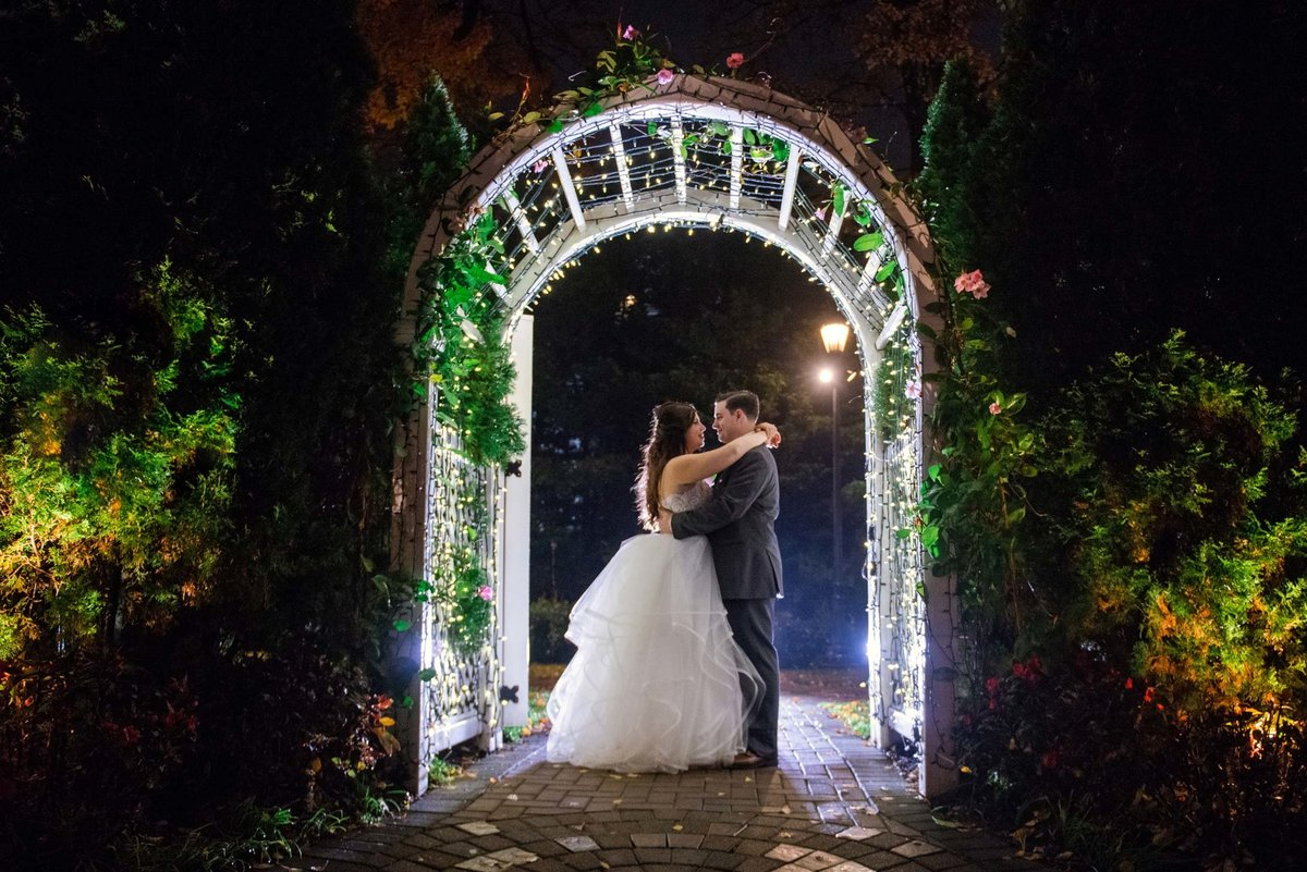 Bride and groom under the arch at Fox Hollow