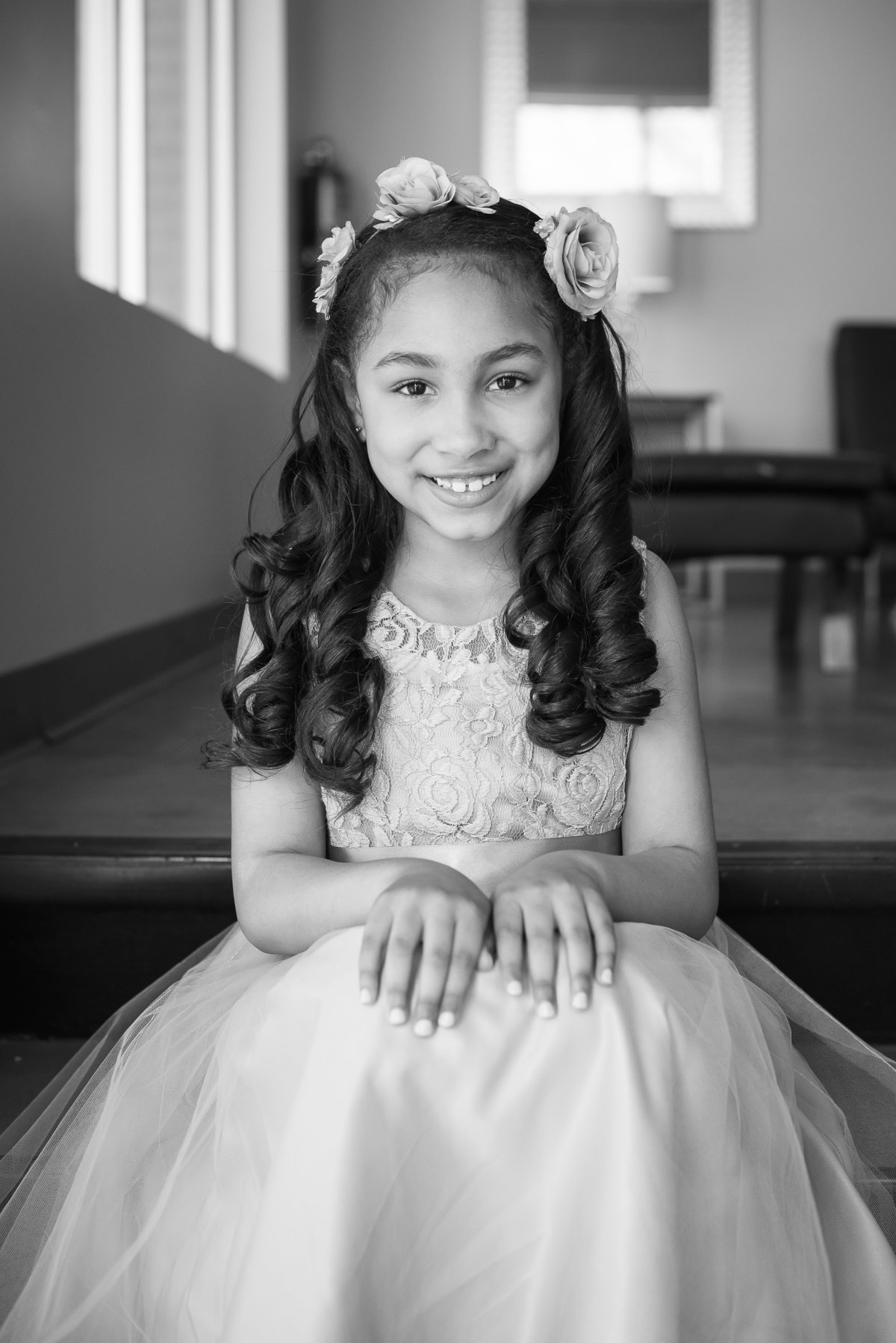 black and white of flower girl sitting on stairs
