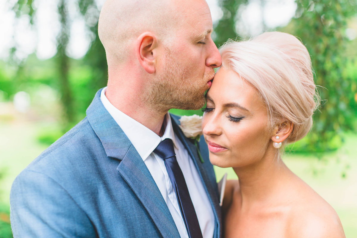 natural wedding photo of groom in blue suit kissing the bride