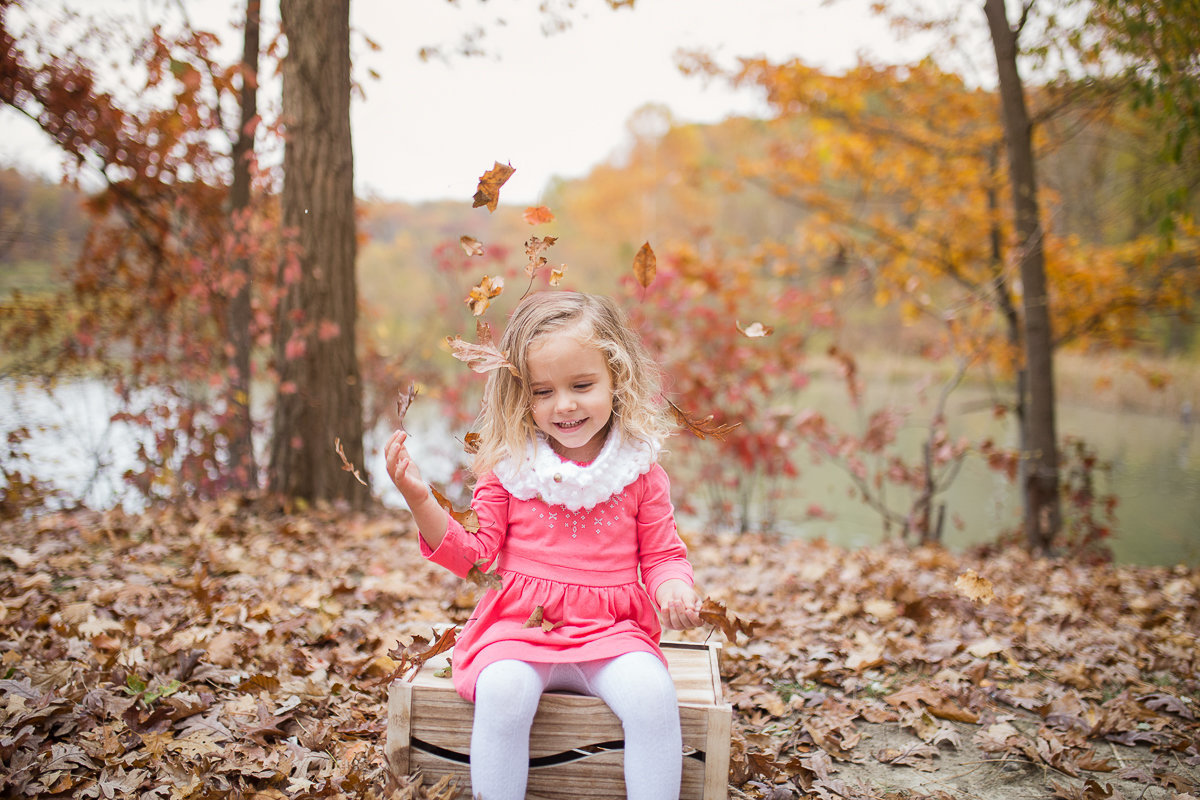 three year old girl tossing leaves outdoors {Oakville Child Photographer}