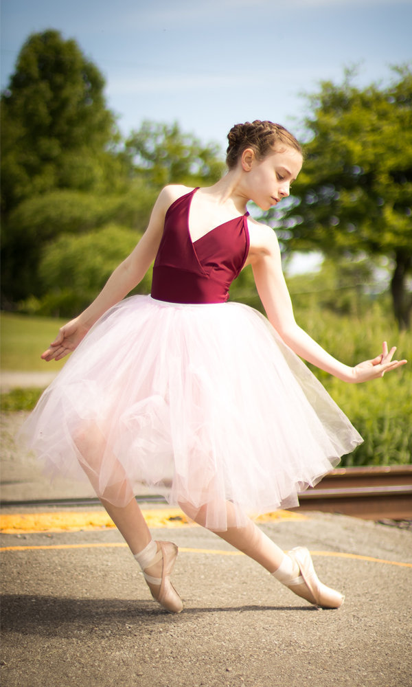 Ballet dancer in street surrounded by green forest