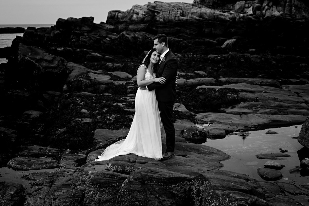 Cape Elizabeth Elopement the newlyweds stand on the rocks in front of the Portland Headlight in Maine