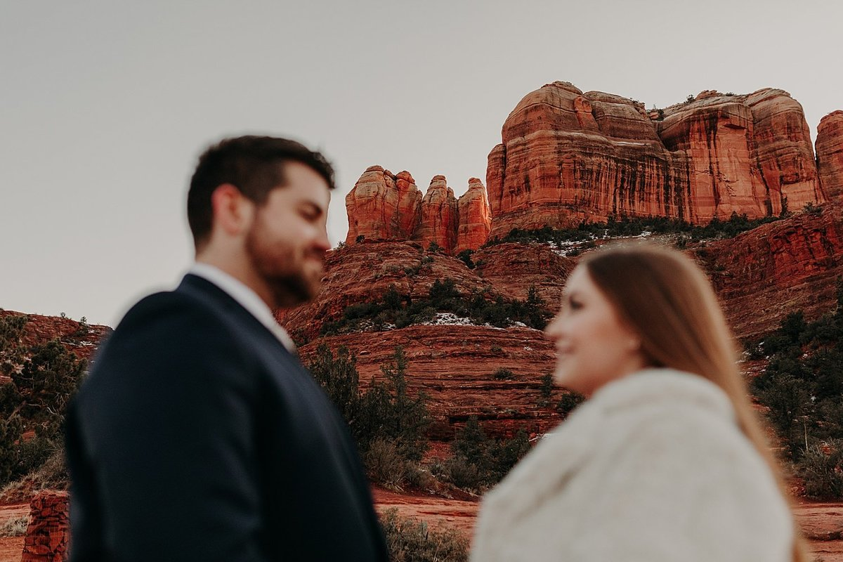 Blurry couple face each other while the sedona red rocks are in focus on the background