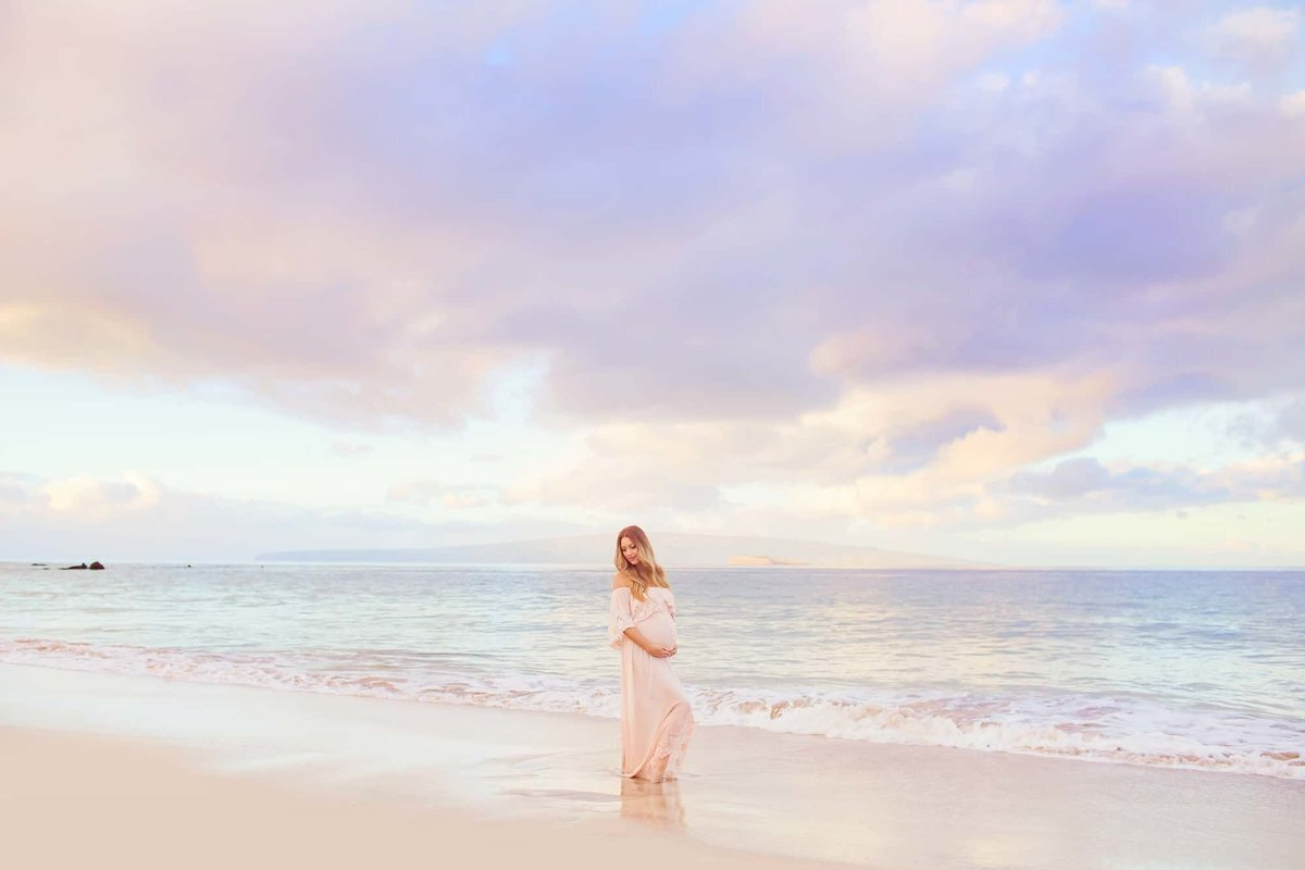 Maui maternity portrait of woman wearing a pink gown at sunrise on the beach