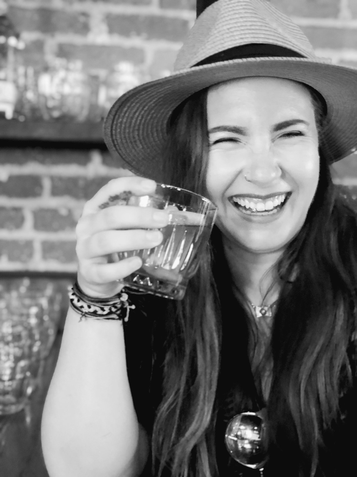 Girl laughs while drinking whiskey