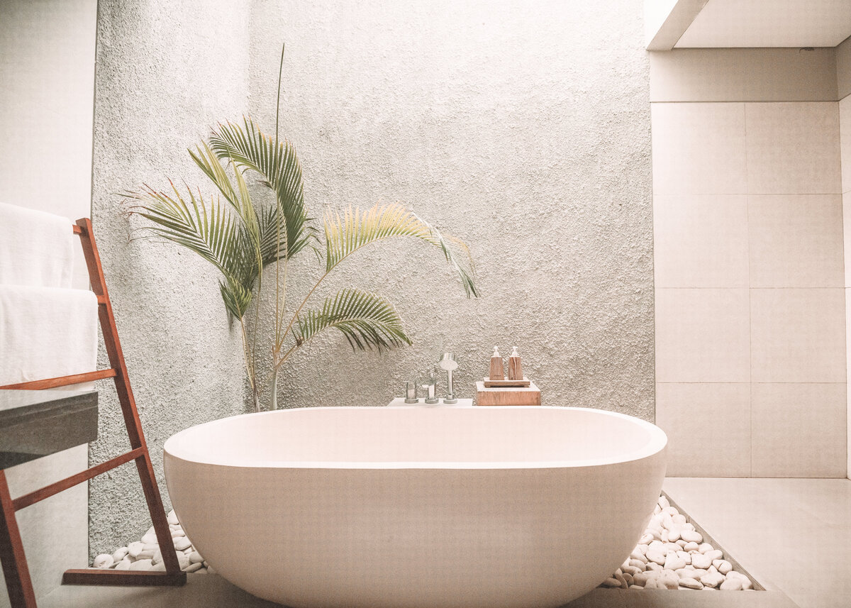 A freestanding modern bathtub is placed on concrete and pebbles outside, next to a wooden towel rail.