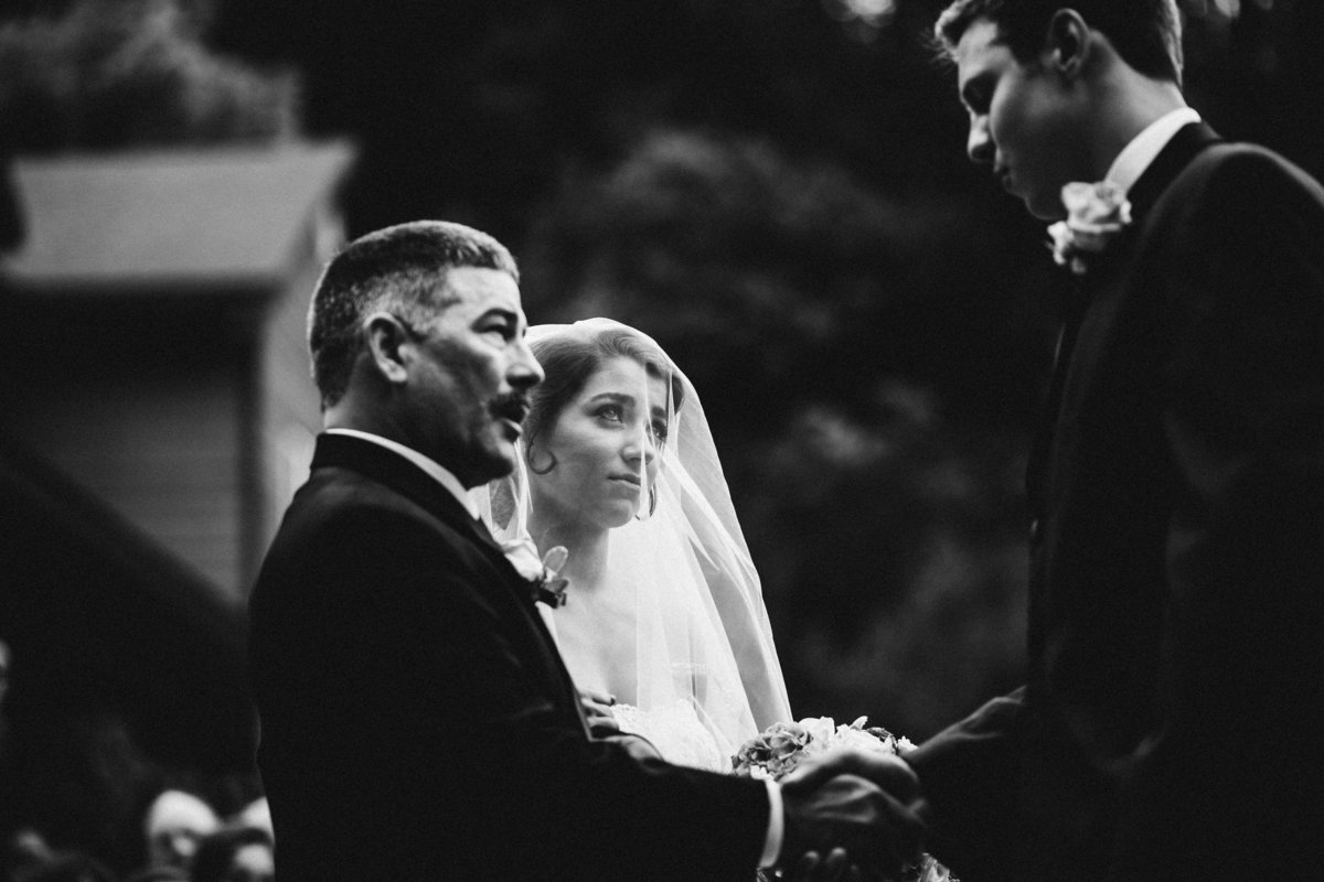 bride with tears in her eyes looks at groom who shakes father's hand