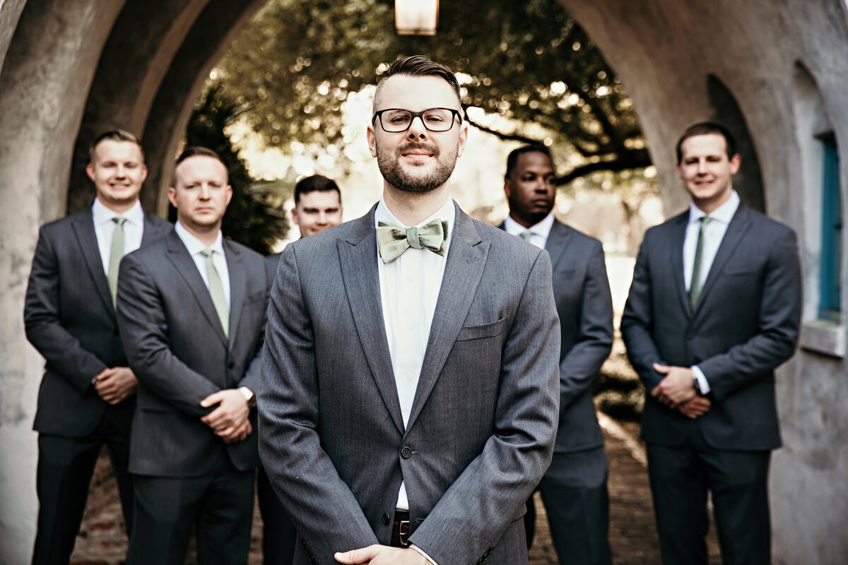A picture of the groom with his groomsmen lined up behind him standing in their handsome suits and ties under a vintage archway by Garry & Stacy Photography Co - St Petersburg Florida wedding photographer
